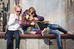Amigos jovenes que se relajan contra una fuente de la ciudad Fotografía de archivo