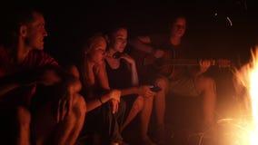 Amigos jovenes que se sientan cerca de las canciones de la hoguera y del canto con una guitarra en la noche almacen de metraje de vídeo