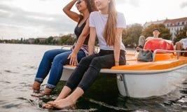 Amigos jovenes que se sientan en barco del pedal Fotos de archivo libres de regalías