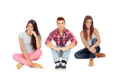 Amigos jovenes que se sientan en el piso Fotos de archivo libres de regalías