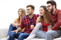 Amigos jovenes que se sientan en el sofá y que arraigan para su equipo preferido Foto de archivo libre de regalías