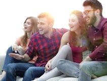 Amigos jovenes que se sientan en el sofá y que arraigan para su equipo preferido Fotos de archivo libres de regalías