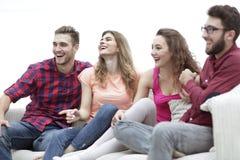 Amigos jovenes que se sientan en el sofá y que arraigan para su equipo preferido Imagenes de archivo
