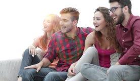 Amigos jovenes que se sientan en el sofá y que arraigan para su favorit Imagen de archivo libre de regalías
