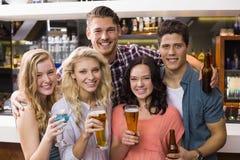 Amigos jovenes que tienen una bebida junto Foto de archivo libre de regalías