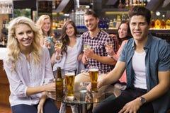 Amigos jovenes que tienen una bebida junto Fotos de archivo libres de regalías