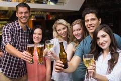 Amigos jovenes que tienen una bebida junto Imágenes de archivo libres de regalías