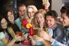 Amigos jovenes que tienen una bebida junto Foto de archivo