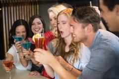 Amigos jovenes que tienen una bebida junto Imagen de archivo libre de regalías