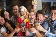Amigos jovenes que tienen una bebida junto Imagen de archivo