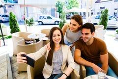 Amigos jovenes que toman el selfie mientras que se sienta en el café Imagen de archivo