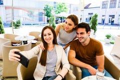 Amigos jovenes que toman el selfie mientras que se sienta en el café Fotos de archivo