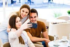 Amigos jovenes que toman el selfie mientras que se sienta en el café Imagen de archivo libre de regalías