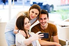 Amigos jovenes que toman el selfie mientras que se sienta en el café Imágenes de archivo libres de regalías