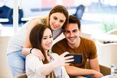 Amigos jovenes que toman el selfie mientras que se sienta en el café Foto de archivo