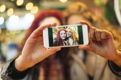 Amigos jovenes que toman un selfie con el teléfono móvil Fotografía de archivo libre de regalías