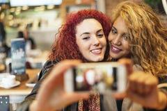 Amigos jovenes que toman un selfie con el teléfono móvil Foto de archivo libre de regalías