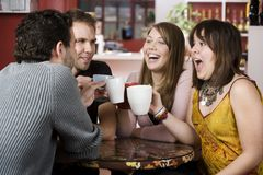 Amigos jovenes que tuestan con las tazas de café Imagenes de archivo