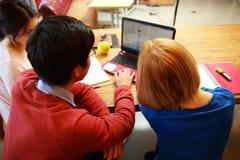 Amigos jovenes que usan el ordenador portátil junto Imagenes de archivo