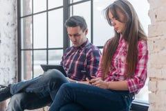 Amigos jovenes que usan juego del app con sus smartphones Foto de archivo
