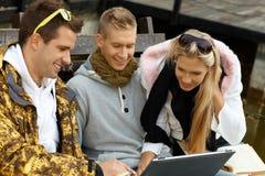 Amigos jovenes que usan la computadora portátil al aire libre Fotografía de archivo
