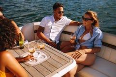 Amigos jovenes que van de fiesta en un barco Fotografía de archivo libre de regalías