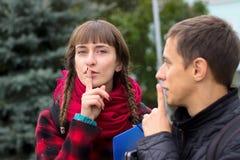 Amigos jovenes serios del estudiante que hablan en la universidad Shh gesto Fotografía de archivo libre de regalías