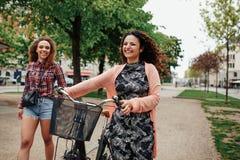 Amigos jovenes sonrientes con la bicicleta que caminan en la calle de la ciudad Fotos de archivo libres de regalías