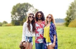 Amigos jovenes sonrientes del hippie en campo verde Foto de archivo