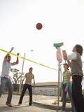 Amigos jovenes sonrientes que juegan a voleibol en calle imagen de archivo libre de regalías