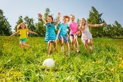 Amigos juguetones que corren a la bola en campo Foto de archivo