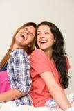 Amigos juguetones que se sientan continuamente y que ríen Imagenes de archivo