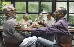 Amigos maduros en un partido de cena imagen de archivo libre de regalías