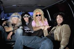 Amigos masculinos alegres que se sientan en una limusina Foto de archivo