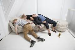 Amigos masculinos borrachos que duermen en el sofá de la piel después de partido fotografía de archivo