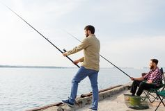 Amigos masculinos com as varas de pesca no cais do mar fotografia de stock