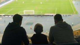 Amigos masculinos con el niño que mira reservado fútbol en el estadio, juego del taladro, derrota almacen de metraje de vídeo