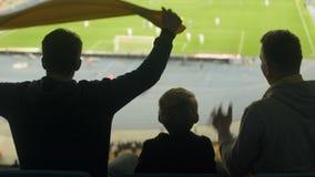 Amigos masculinos con fútbol de observación del niño en el estadio, la adrenalina y las emociones almacen de metraje de vídeo