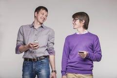 Amigos masculinos con los teléfonos a disposición Fotografía de archivo