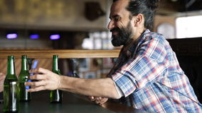 Amigos masculinos con smartphones que beben la cerveza en la barra almacen de metraje de vídeo