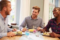 Amigos masculinos em casa que sentam-se em torno da tabela para o partido de jantar foto de stock royalty free
