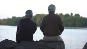 Amigos masculinos envejecidos que se sientan junto afuera, mirando horizonte del río, tranquilidad almacen de video