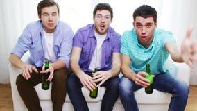 Amigos masculinos felices con la cerveza que ven la TV en casa almacen de metraje de vídeo