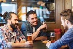 Amigos masculinos felices que beben la cerveza en la barra o el pub Foto de archivo libre de regalías