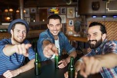 Amigos masculinos felices que beben la cerveza en la barra o el pub Fotos de archivo libres de regalías