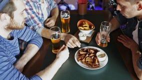 Amigos masculinos felices que beben la cerveza en la barra o el pub almacen de video