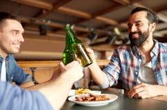 Amigos masculinos felices que beben la cerveza en la barra o el pub fotos de archivo