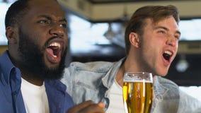 Amigos masculinos felices que tintinean los vidrios de cerveza, partido de observación en barra, celebración almacen de video