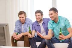 Amigos masculinos felizes com cerveja que olham a tevê em casa fotografia de stock