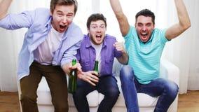 Amigos masculinos felizes com cerveja que olham a tevê em casa vídeos de arquivo